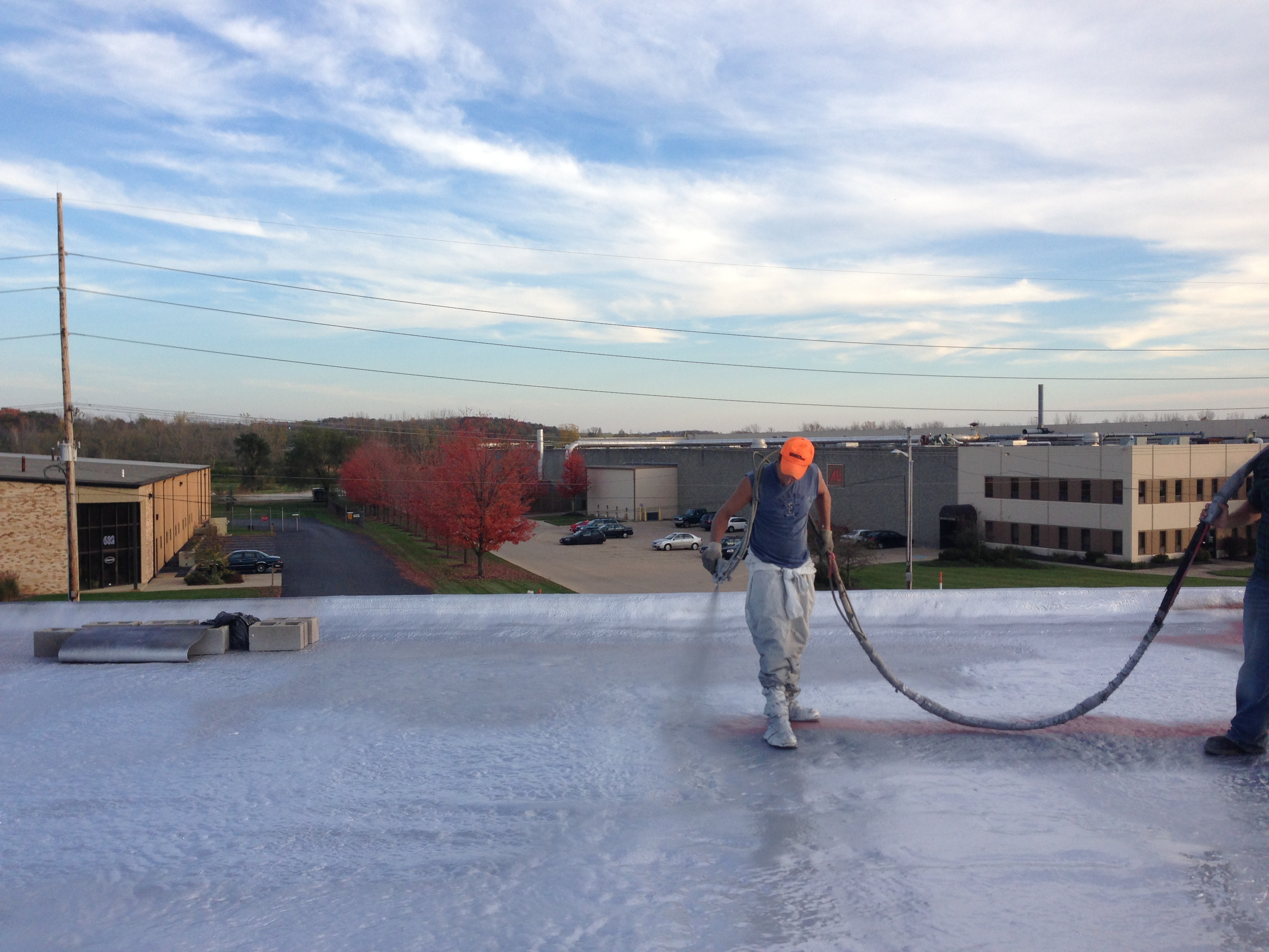 "Spraying silver polyurea topcoat on 2"" SPF roof."